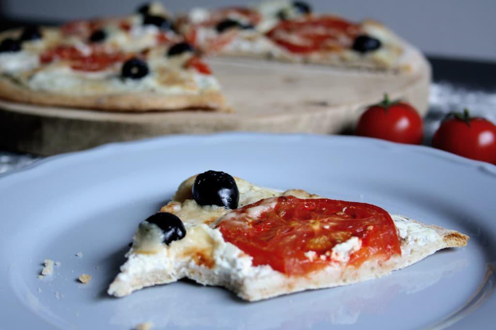 Pizza mit Ziegenfrischkäse, Tomaten und Oliven