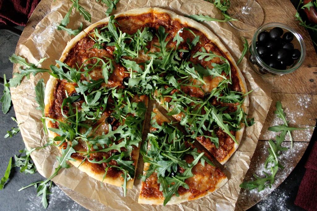 Pizza mit Mozzarella, Oliven & Rucola