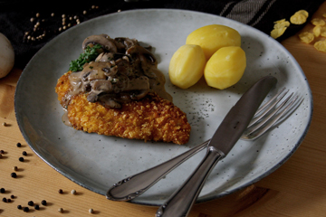 Knusprige Hähnchenschnitzel mit cremigen Champignons