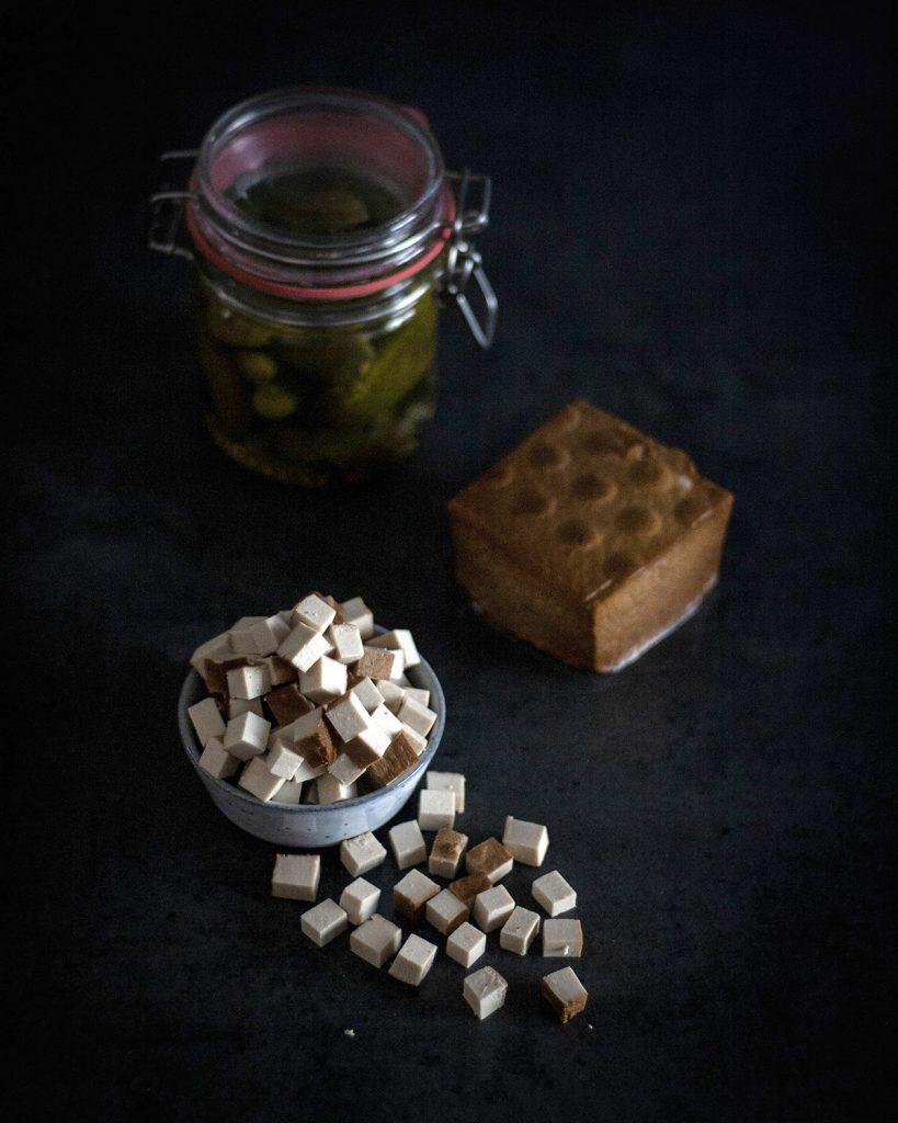 Räuchertofu gewürfelt und am Stück, Gewürzgurken im Glas: Zutaten für Kartoffelbrei mit geschmorten Zwiebeln, Gurken & Räuchertofu