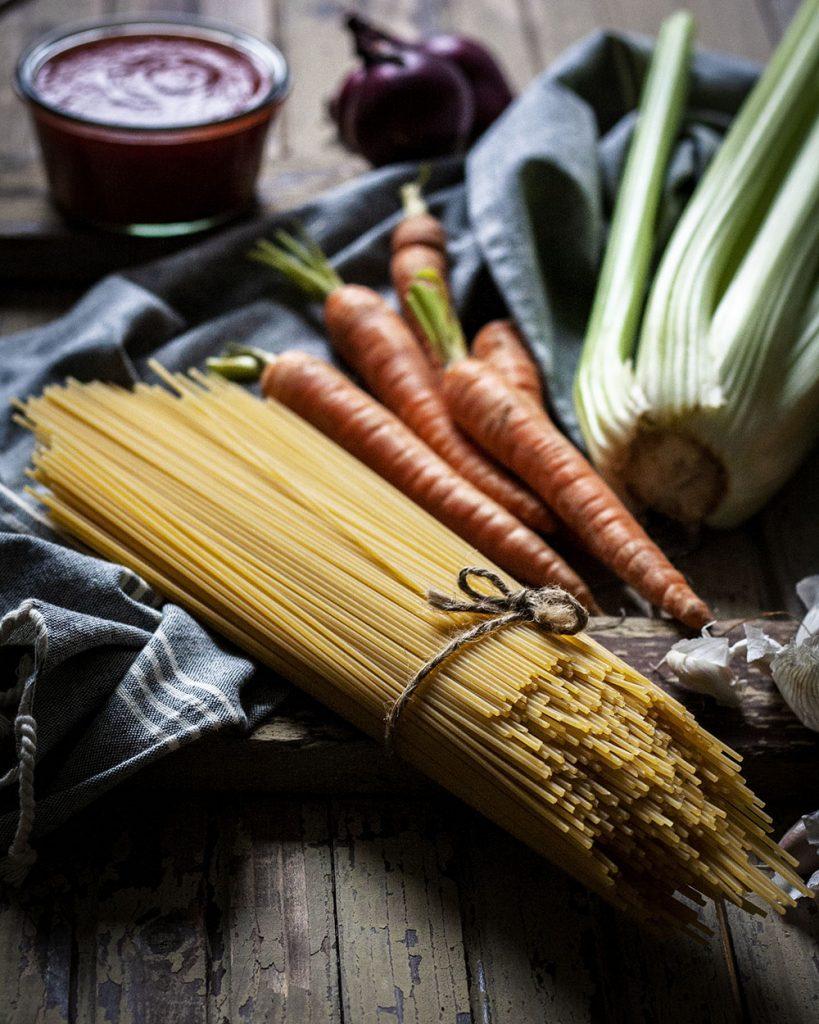 Spaghetti, Möhren, Sellerie, Zwiebeln und Tomaten - Zutaten für vegane Tomatensauce