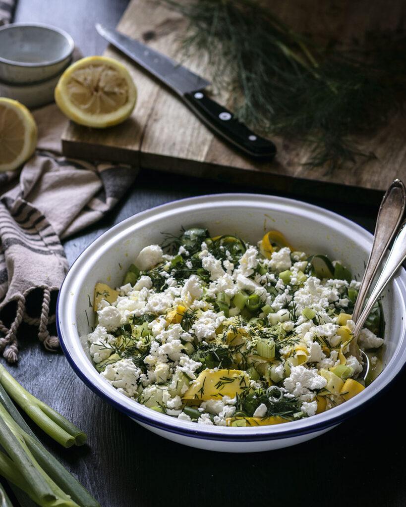 Würziger Fetakäse, reichlich Dill und knackige Lauchzwiebeln machen diesen Gurken-Zucchini-Salat zum absoluten Sommerrezept