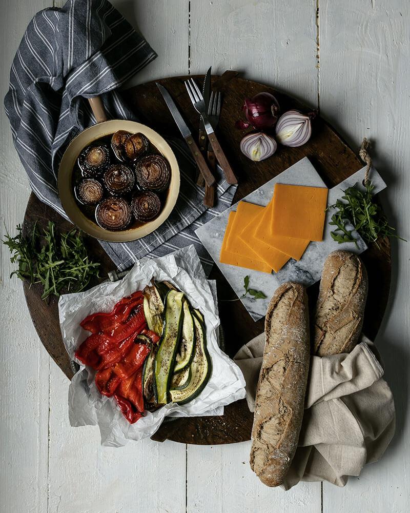Geschmorte Zwiebeln, Ofengemüse, Käse, Baguette & Rucola: Zutaten für belegtes Baguette mit gegrilltem Gemüse